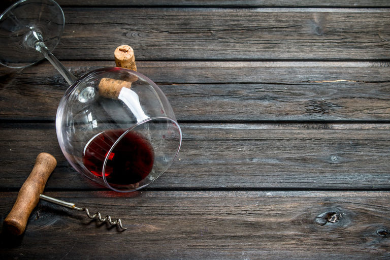 Red wine in a wine glass with a corkscrew.